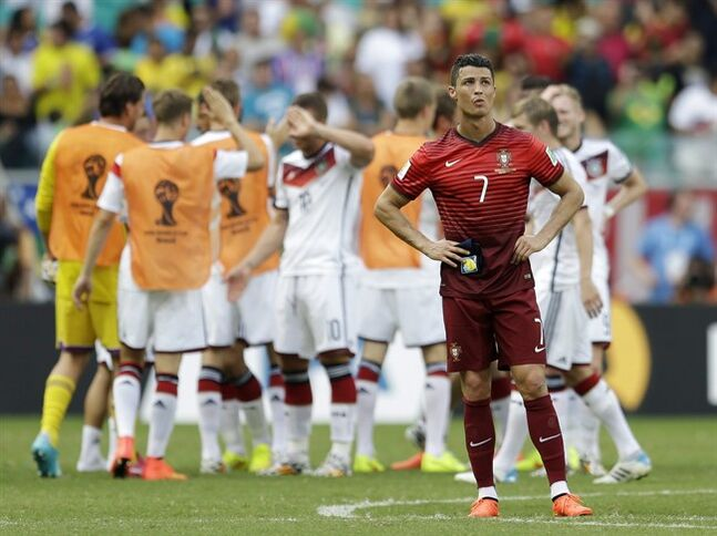 Portugal's Cristiano Ronaldo stands on the pitch as German players celebrate following Portugal's 4-0 loss to Germany during the group G World Cup soccer match between Germany and Portugal at the Arena Fonte Nova in Salvador, Brazil, Monday, June 16, 2014. (AP Photo/Natacha Pisarenko)