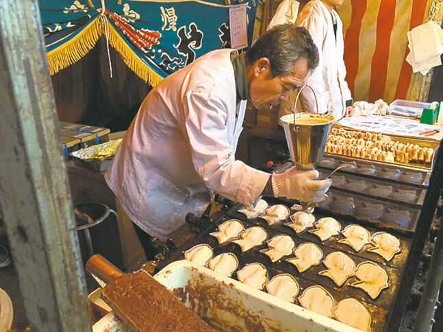 A man makes tai-yaki, which are sweet azuki bean-filled pancakes in the shape of sea bream fish, on a pathway leading to the Kiyoshikojin Seicho-ji temple complex north of Osaka, Japan.