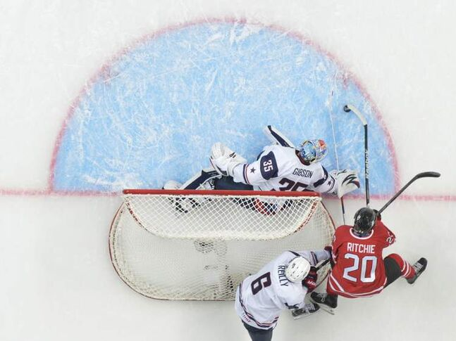 Team Canada forward Brett Ritchie (20) tries for a wrap around on Team USA goalie John Gibson as USA defenceman Mike Reilly keeps close during the first period.
