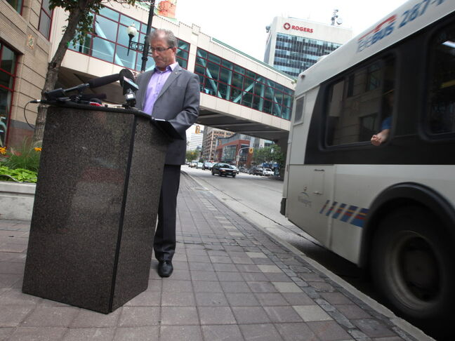 Gord Steeves stands near a bus stop in front of Portage Place Friday afternoon to pledge measures to improve downtown safety.