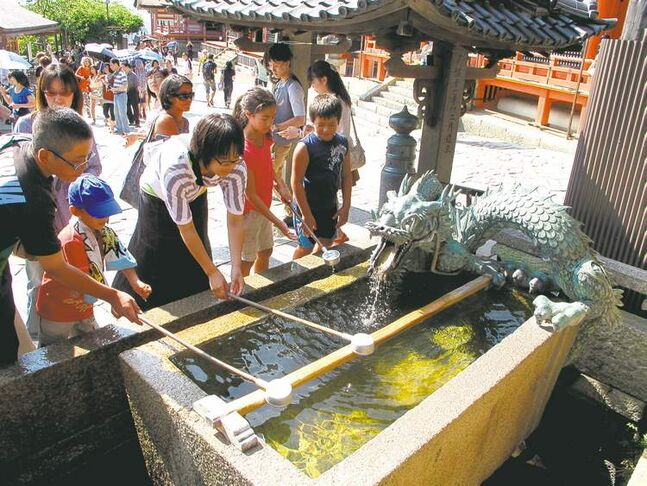 Visitors scoop water from a fountain near the entrance to Kiyomizu Temple in Kyoto. Such fountains are common at Japanese temples, used to wash hands and cleanse the mouth in a brief purification ritual.