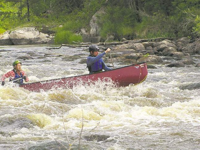 Running a long Class II on the Manigotagan River. Helmets, PFDs and throwbags are the minimum safety gear for running rapids.