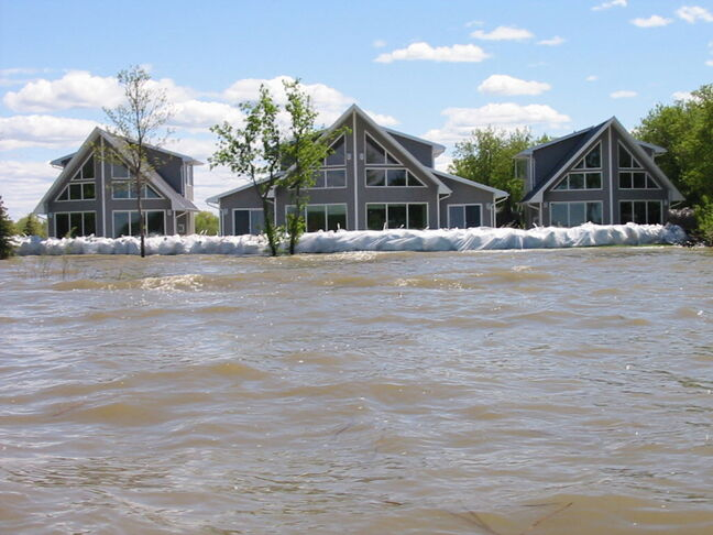 A cottage, flanked by two guest houses, valued at close to $1 million, sits protected behind sandbag dike on Dauphin Lake in June of 2011.