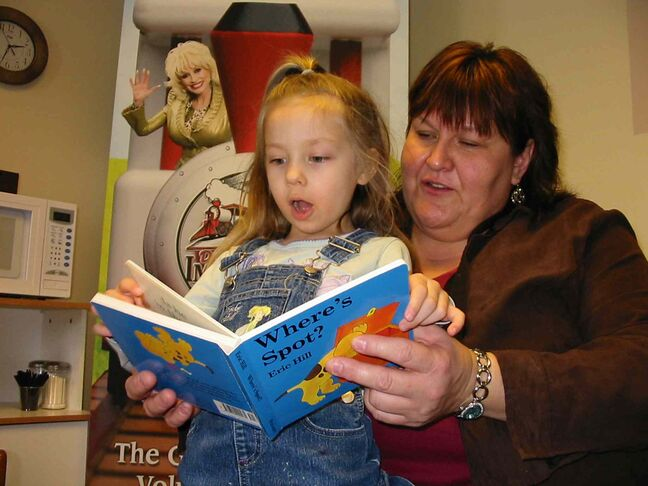 Karen Davis reads a book to Maddie Amoyette, 4. Dolly Parton created a literacy foundation that sends books to kids.