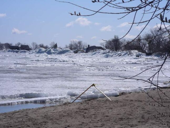 A ridge of ice sits along the shore of Ochre Beach, with nearby homes and cottages in the background.
