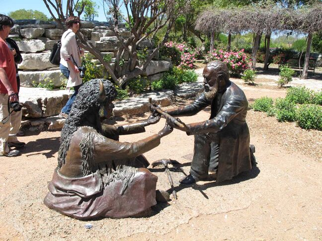 Statue depicting a peace treaty tradition between settlers and Native Americans.