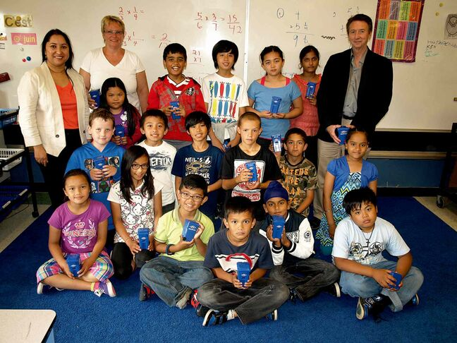 Coun. Devi Sharma (back row, far left) with O.V. Jewitt Community School Grade 4 teacher Laura Veitch (top, second from left)  her students, and O.V. Jewitt principal Bob McIntosh (back row, far right). The students received mini recycling bins as a reminder for them to reduce, reuse and recycle.