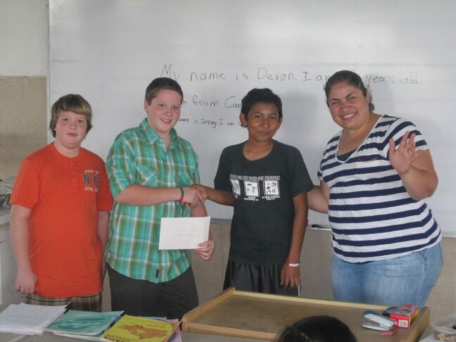 Devon Liscum (second from left) and brother Jeremy (left) pose at a school in Mexico while helping out in the School of Champions program.