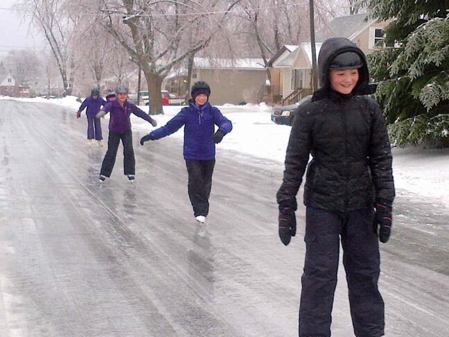 Many flights were delayed yesterday as Eastern Canada cleaned up after an ice storm. Here children skate on an ice-covered street in Kingston, Ont., on Saturday.