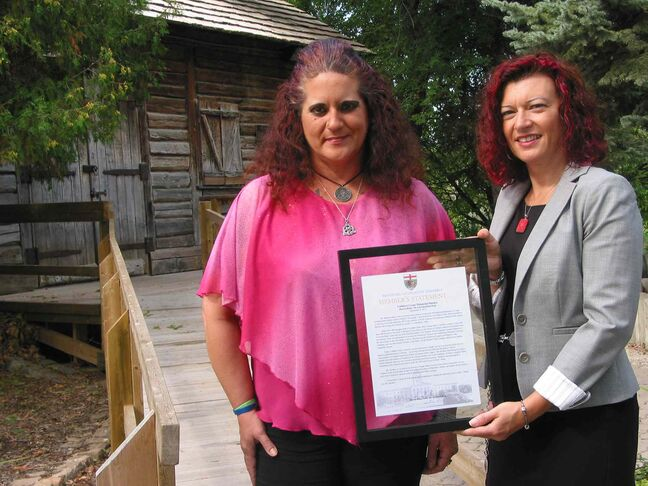Sandra Horyski (left) and MLA Sharon Blady stand in front of Cuthbert Grant's mill in St. James. Blady presented Horyski with a framed copy of the Member's Statement that she'd read in the Manitoba Legislature on Sept. 9 to recognize Horyski's work to raise money for a memorial marker for Grant.