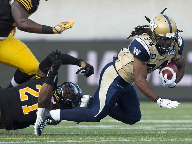 Hamilton Tiger-Cats' linebacker Simoni Lawrence (21) trips up Winnipeg Blue Bombers' running back Paris Cotton (34) during first half of Thursday's game.