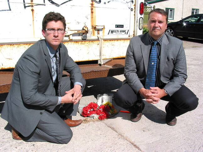 Matt Allard (left) and Staff Sgt. Bob Chrismas observe a tribute to homicide victim Kyle Devasconcelos near the backlane of Dumoulin Street in St. Boniface.