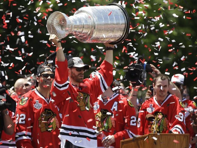 Chicago Blackhawks' Viktor Stalberg, of Sweden, holds up the Stanley Cup as teammates Jamal Mayers, left, and Dave Bolland look on during a rally in Grant Park for the NHL Stanley Cup hockey champions Friday, June 28, 2013, in Chicago. (AP Photo/M. Spencer Green)