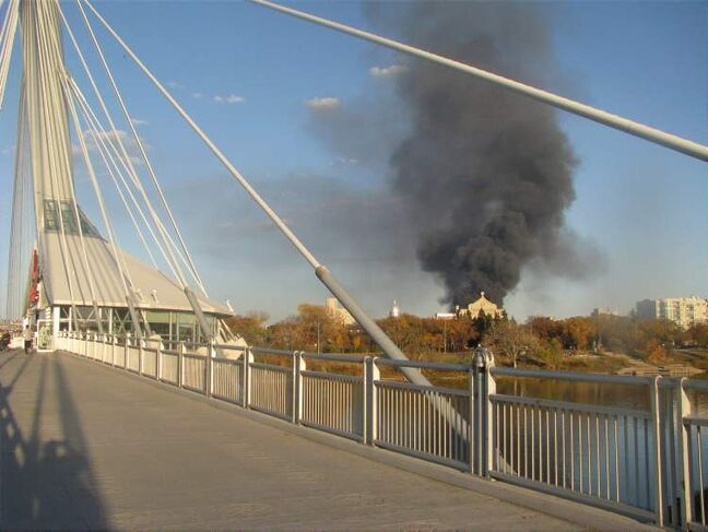 Smoke from the fire is seen from the Esplanade Riel pedestrian bridge over the Red River.