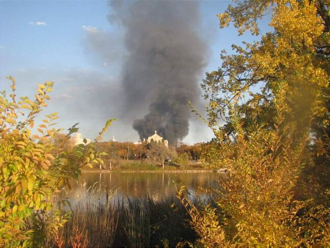 The fire is seen from across the Red River, behind the St. Boniface Cathedral.