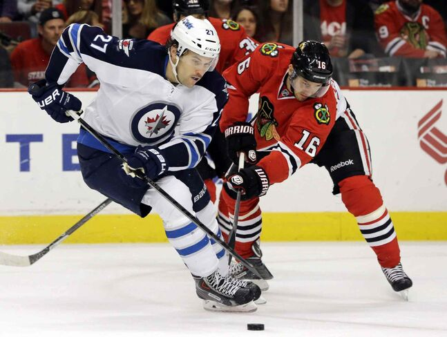 Eric Tangradi (27) of the Winnipeg Jets controls the puck against Chicago Blackhawks' Marcus Kruger (16) during the first period.