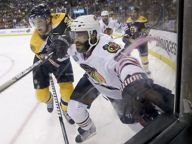 Boston Bruins center Carl Soderberg and Chicago Blackhawks defenceman Johnny Oduya fight for position along the boards during the second period.