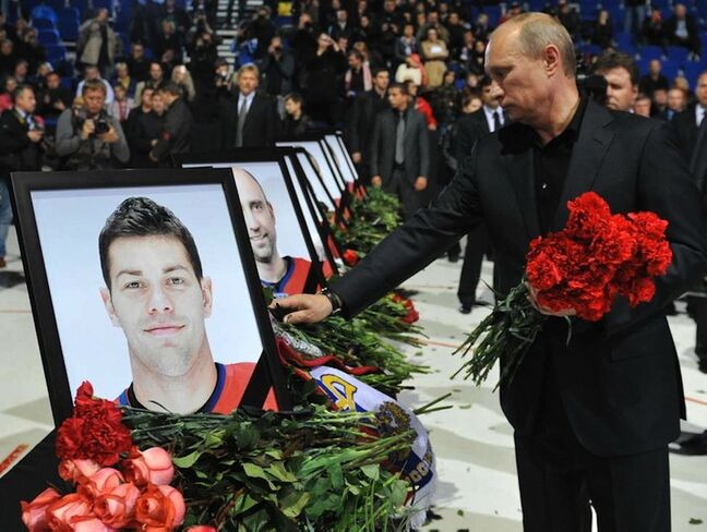 Russian Prime Minister Vladimir Putin lays flowers during a memorial ceremony for the victims of the Russian plane crash in Arena Yaroslavl on Saturday, Sept. 10, 2011.