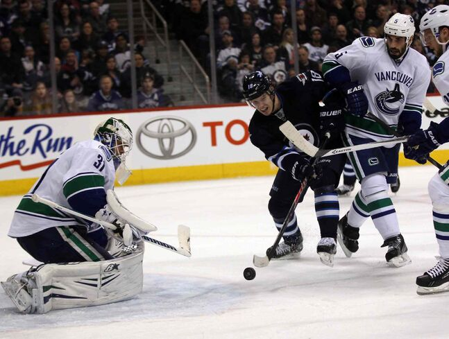 Winnipeg Jets' Bryan Little heads to the net towards Vancouver Canucks' Eddie Lack during the second period of Friday's game in Winnipeg.