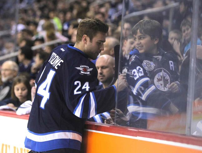 Winnipeg Jets defenceman Grant Clitsome signs a child's jersey. He doesn't seem upset that it's a Dustin Byfuglien jersey.