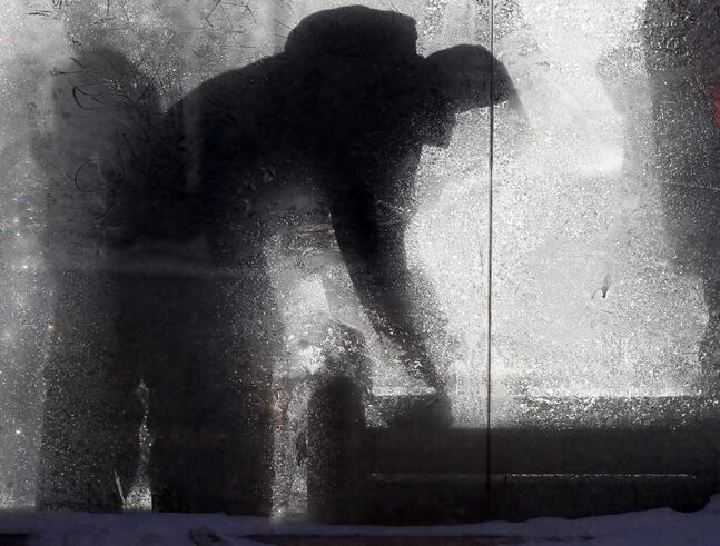 Waiting for a bus in a shelter on Portage Avenue. (JOE BRYKSA / WINNIPEG FREE PRESS)
