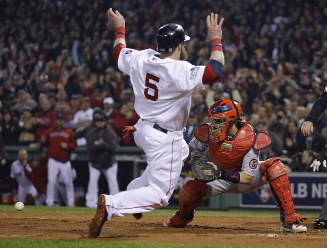 St. Louis Cardinals catcher Yadier Molina waits for the throw as Boston Red Sox's Jonny Gomes heads for home plate.