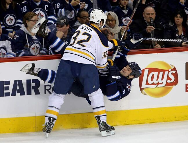 Buffalo Sabres' John Scott (32) flattens Winnipeg Jets' Mark Stuart (5) during first period NHL hockey action in Winnipeg. 