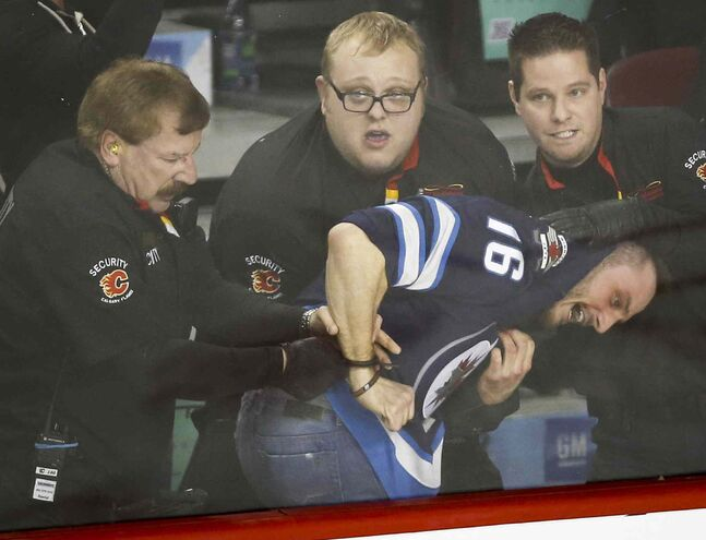 Security officials subdue and handcuff a Winnipeg Jets fan after a fight broke out during third period NHL hockey action against the Calgary Flames in Calgary Thursday. The Winnipeg Jets beat the Calgary Flames 5-2.