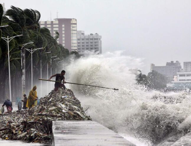 A man holding a pole stands on a mound of garbage washed ashore by big waves as others look for recyclable materials Wednesday, Aug. 1, 2012 along Roxas Blvd. in Manila, Philippines. The slow-moving Typhoon Saola killed at least 12 people and displaced 154,000 in the Philippines.  AP Photo / Pat Roque