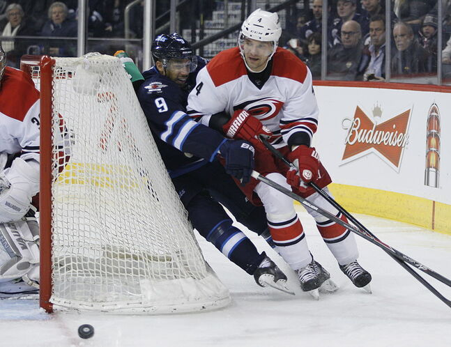 Winnipeg Jets' Evander Kane (9) gets injured as he boes around the net with Carolina Hurricanes' Andrej Sekera (4).