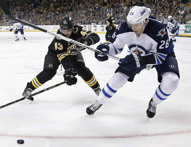 Boston Bruins' Matt Bartkowski (43) and Winnipeg Jets' Blake Wheeler (26) battle for the puck in the first period of NHL action in Boston Saturday.