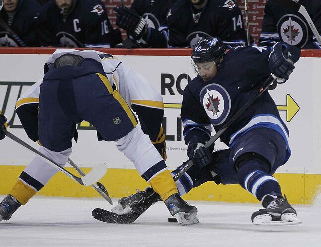 Winnipeg Jets' Devin Setoguchi (40) fights for the puck with Nashville Predators' Patric Hornqvist (27) during the second period of Tuesday's game at MTS Centre.