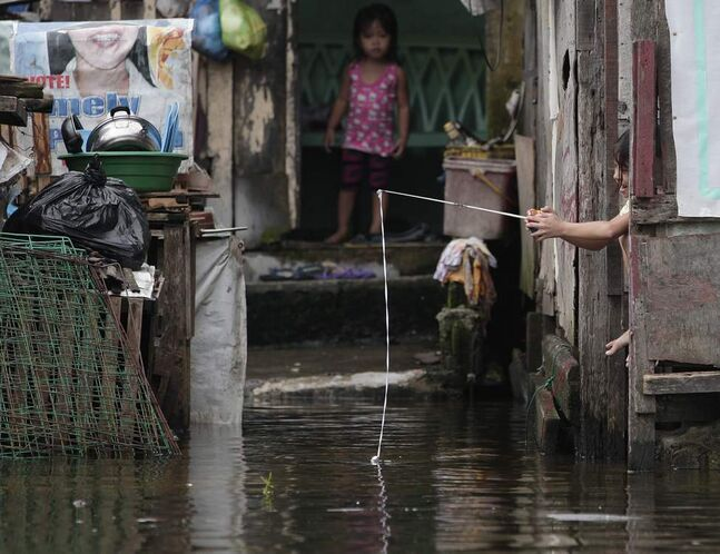 A Filipino girl plays with a mock fishing rod outside their flooded home at Valenzuela city, north of Manila, Philippines on Tuesday July 31, 2012. Typhoon Saola dumped torrents of rain as it swept past the Philippines, killing at least seven people and displacing more than 20,000 others by Tuesday.  AP Photo / Aaron Favila