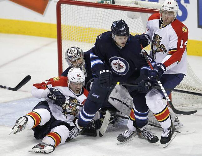Winnipeg Jets defenceman Ron Hainsey deals with Florida Panthers Tomas Kopecky (left) and Tomas Fleischmann in front of Jets goaltender Ondrej Pavelec during third-period NHL action in Winnipeg Thursday.
