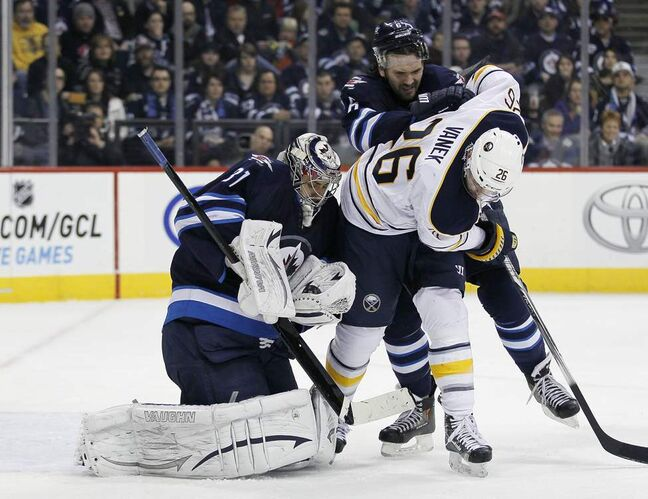 Winnipeg Jets' goaltender Ondrej Pavelec (31) snags the Buffalo shot as Jets' Ron Hainsey (6) drives Buffalo Sabres' Thomas Vanek (26) off the puck during first period NHL action in Winnipeg. 