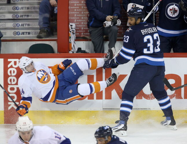 New York Islanders' Thomas Hickey (14) flies after being checked by Winnipeg Jets' Dustin Byfuglien (33) during the first period.