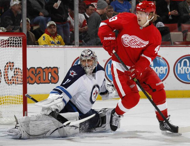 Detroit Red Wings forward Darren Helm pursues the puck in front of Winnipeg Jets goalie Ondrej Pavelec during the first period.