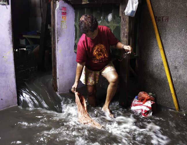 A woman watches floodwater flow into a house following a dike breach caused by the storm, Friday, Aug. 4, 2012 in Navotas City, north of Manila, Philippines. Typhoon Saola left more than two dozens of people dead and forced 180,000 to flee their homes in the country.   AP Photo / Pat Roque