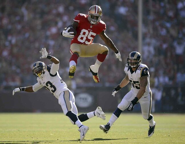 San Francisco 49ers tight end Vernon Davis (85) leaps over St. Louis Rams free safety Rodney McLeod (23) and St. Louis Rams middle linebacker James Laurinaitis (55) after a pass reception in the first quarter at Candlestick Park on Sunday, Dec. 1, 2013.