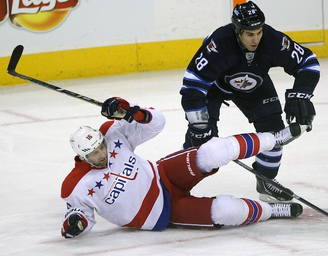 Patrice Cormier of the Winnipeg Jets is tied up with Washington Capitals (and ex-Jets) forward Eric Fehr during first-period action in Friday night's game.