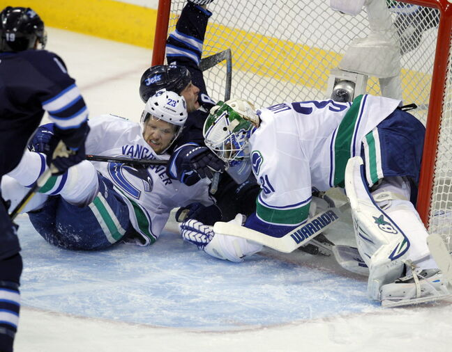 Jacob Trouba (8) crashes into the net between Canucks Alexander Edler  (23) and goalie Eddie Lack.