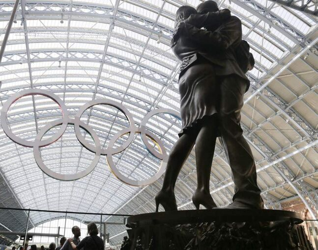 A couple pauses at the foot of a statue with the Olympic rings hung in the rafters of St. Pancras Station prior to the 2012 Summer Olympics in London. The opening ceremonies for the 2012 London Olympics will be held Friday. (AP Photo/Charles Krupa)