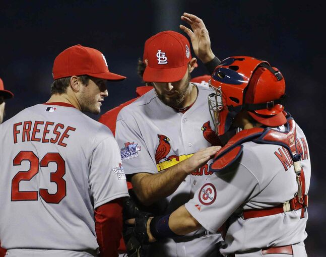 St. Louis Cardinals third baseman David Freese (left) watches as catcher Yadier Molina (right) pats starting pitcher Michael Wacha on the head as he is taken out of the game during the fourth inning.