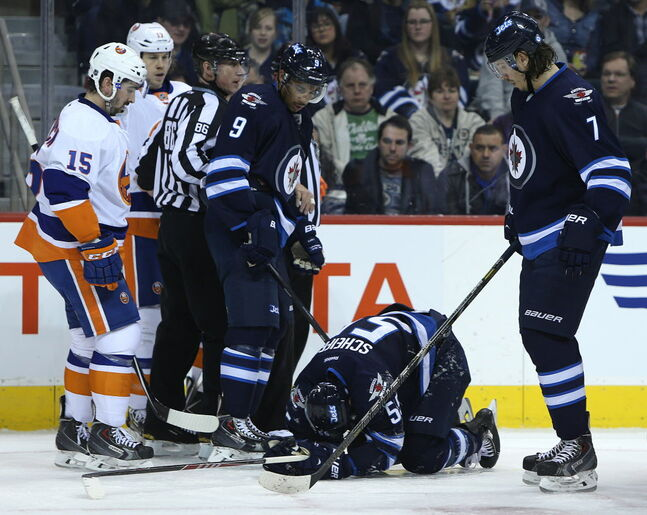 Winnipeg Jets forward Evander Kane and defenceman Keaton Ellerby look at Mark Scheifele after he was injured during the second period.