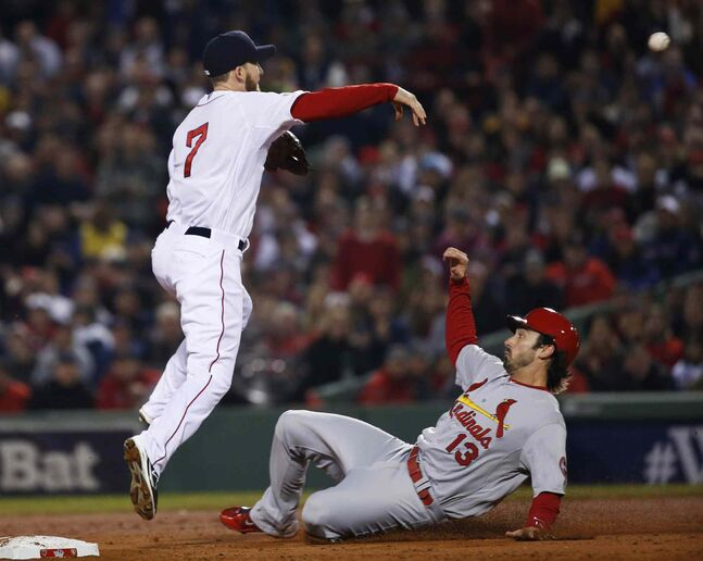 Boston Red Sox short stop Stephen Drew (left) throws over St. Louis Cardinals' Matt Carpenter to turn a double play on a hit by Carlos Beltran during the third inning.
