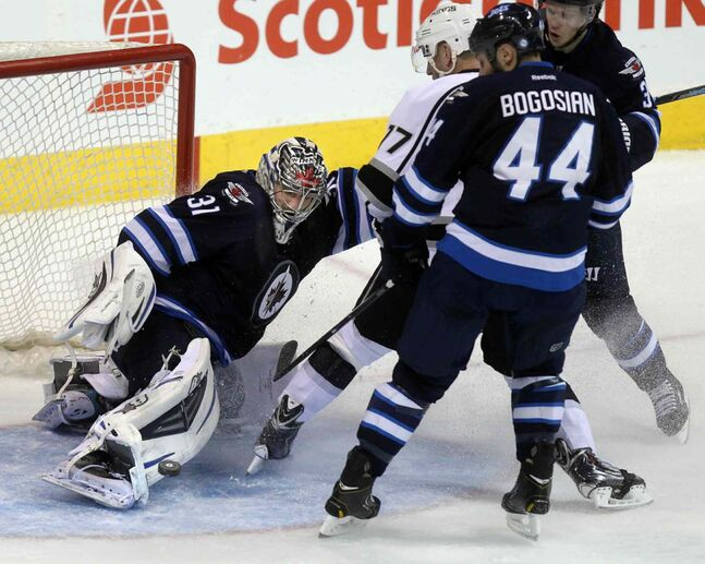 Ondrej Pavelec covers up as Zach Bogosian, Tobias Engstrom and Los Angeles King Jeff Carter slide to a stop in the crease in the third period.