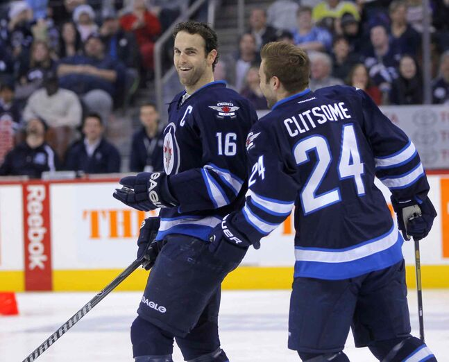 Andrew Ladd and Grant Clitsome have a laugh on the ice.