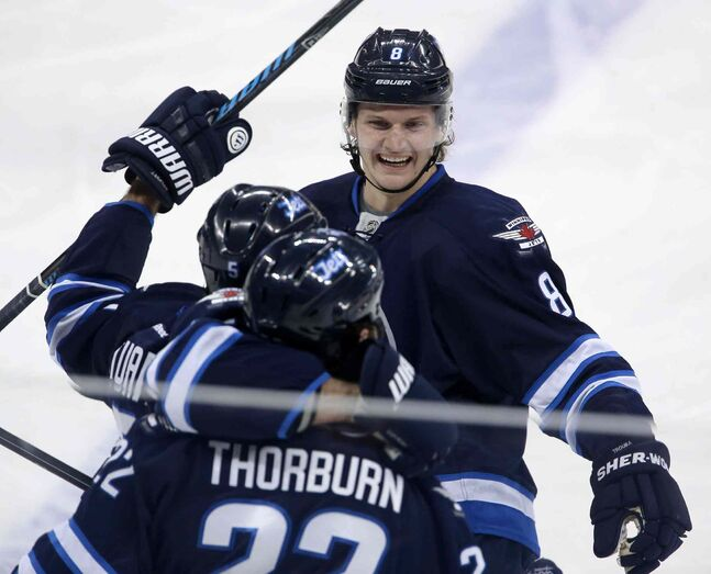 Winnipeg Jets' Jacob Trouba (8), Mark Stuart (5) and Chris Thorburn (22) celebrate Thorburn's first goal of the season during the  first period of Tuesday's game against the Nashville Predators in Winnipeg.