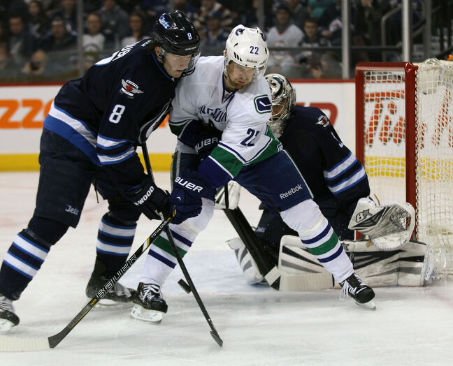 Winnipeg Jets' Jacob Trouba ties it up with Vancouver Canucks' Daniel Sedin during the first period of Friday's game in Winnipeg.