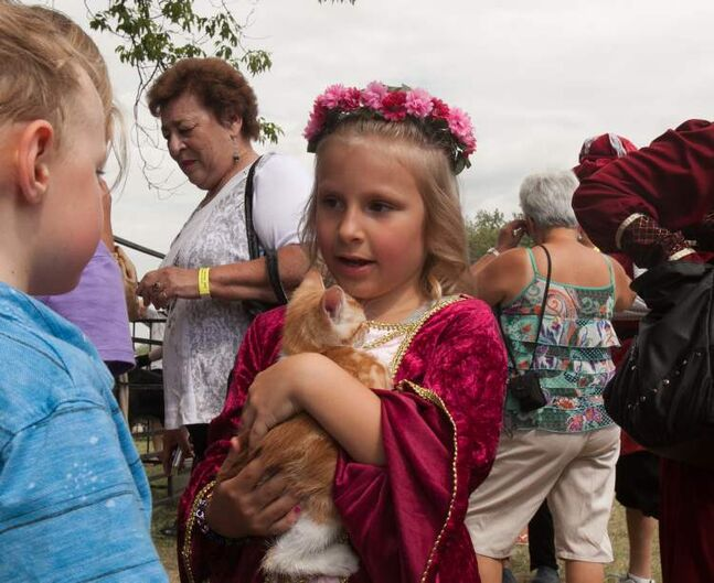 Kiya Taylor, dressed in medieval garbs, cradles a kitten at the 2012 Medieval Festival at the Immaculate Conception Church and Grotto on Saturday in Cooks Creek.